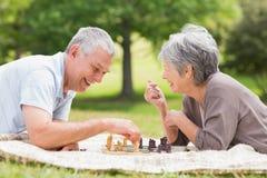 Lyckliga höga par som spelar schack på parkera Royaltyfri Foto