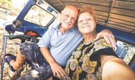 Lyckliga höga par som tar selfie på trehjulingen i Filippinerna, reser - begreppet av aktiv skämtsam åldring under avgång - royaltyfri fotografi