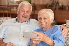 Lyckliga höga par som tillsammans tar selfies på deras mobiltelefon arkivbild