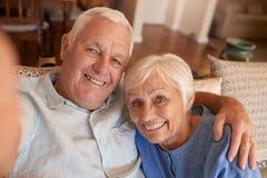 Lyckliga höga par som tillsammans tar selfies på deras soffa arkivfoto