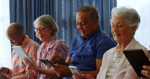 Lyckliga höga vänner som använder den digitala minnestavlan i vardagsrum 4k arkivfilmer
