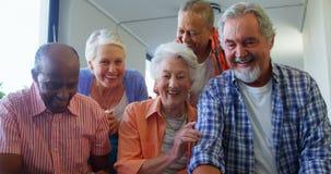 Lyckliga höga vänner som har gyckel, medan genom att använda bärbara datorn 4k arkivfilmer