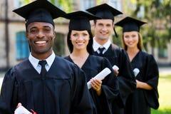 Lyckliga högskolakandidater royaltyfri fotografi