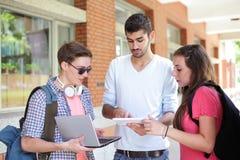 Lyckliga högskolestudenter som använder datoren Royaltyfri Fotografi