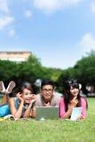 Lyckliga högskolestudenter som använder datoren Royaltyfria Foton