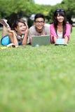 Lyckliga högskolestudenter som använder datoren Fotografering för Bildbyråer