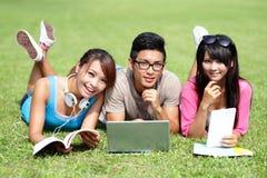 Lyckliga högskolestudenter som använder datoren Royaltyfri Bild