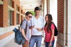 Lyckliga högskolestudenter som använder datoren Arkivfoto