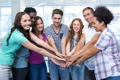 Lyckliga högskolestudenter som tillsammans förlägger händer Arkivfoton