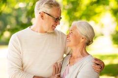 Lyckliga h?ga par som kramar p? sommar, parkerar royaltyfri fotografi