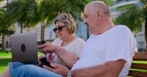 Lyckliga h?ga par som sitter p? en b?nk i sommaren i en modern stad med en b?rbar dator p? bakgrunden av skyskrapor lager videofilmer