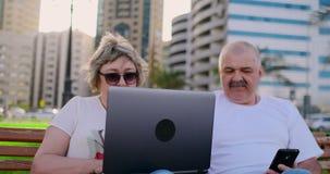 Lyckliga h?ga par som sitter p? en b?nk i sommaren i en modern stad med en b?rbar dator p? bakgrunden av skyskrapor arkivfilmer