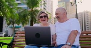 Lyckliga h?ga par som sitter p? en b?nk i sommaren i en modern stad med en b?rbar dator bland palmtr?den p? arkivfilmer