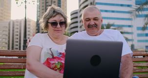 Lyckliga h?ga par som sitter p? en b?nk i sommaren i en modern stad med en b?rbar dator bland palmtr?den p? stock video