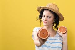 Lyckliga h?llande apelsiner f?r ung kvinna royaltyfri bild