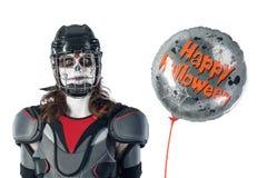 lyckliga halloween hockeyspelare i en hockeyhjälm och maskering med en ballong mot den isolerad bakgrunden eller bakgrund All hel Arkivbild
