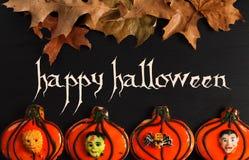 Lyckliga halloween pepparkakakakor på den svarta trätabellen Royaltyfria Foton