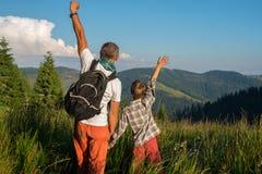 Lyckliga handelsresande: en man och en pojke står under frodigt gräs Royaltyfria Foton