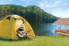Lyckliga handelsresandelivsstilkvinnor på semester som campar med tält som spelar gitarren i skogen nära floden arkivbild
