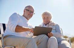 Lyckliga höga par med minnestavlaPC på sommar sätter på land Royaltyfri Bild