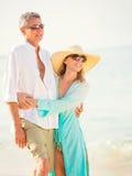 Lyckliga höga par på stranden. Avgång lyxig tropisk Res Arkivbilder