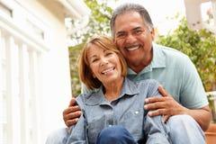 Lyckliga höga par som kopplar av i trädgård Royaltyfria Foton