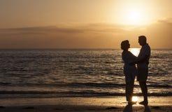 Lyckliga höga par som omfamnar på solnedgångstranden Arkivbild