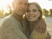 Lyckliga höga par som omfamnar på stranden Royaltyfri Fotografi