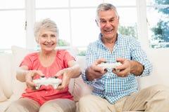 Lyckliga höga par som spelar videospel Arkivfoton