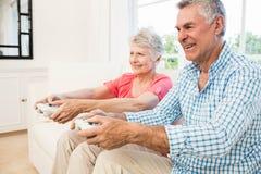 Lyckliga höga par som spelar videospel Royaltyfri Bild