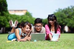 Lyckliga högskolestudenter som använder datoren Arkivfoton
