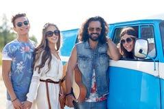 Lyckliga hippievänner med gitarren över minivanbilen royaltyfri foto