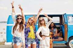 Lyckliga hippievänner som har gyckel över minivanbilen Royaltyfri Bild