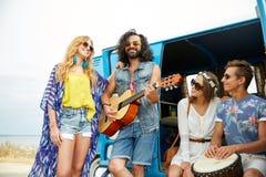 Lyckliga hippievänner som spelar musik över minivan Royaltyfri Bild