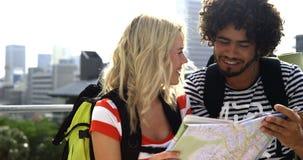 Lyckliga hipsterpar som ser en översikt och pekar riktningen lager videofilmer