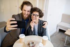 Lyckliga hipsterpar som tar selfie i kafé royaltyfria bilder