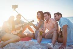 Lyckliga hipsters som tar bilder med selfiepinnen arkivbilder