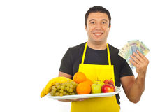 lyckliga holdingpengar för grönsakshandlare arkivbilder