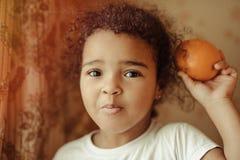 lyckliga home lilla apelsiner för barnfruktflicka Lycklig liten flicka med frukt Arkivfoton