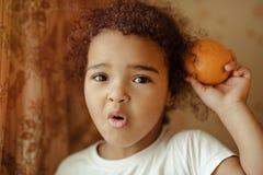 lyckliga home lilla apelsiner för barnfruktflicka Lycklig liten flicka med frukt Royaltyfri Fotografi