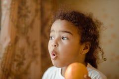 lyckliga home lilla apelsiner för barnfruktflicka Lycklig liten flicka med frukt Fotografering för Bildbyråer