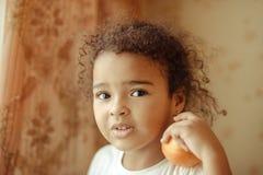 lyckliga home lilla apelsiner för barnfruktflicka Lycklig liten flicka med frukt Royaltyfria Bilder