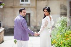 Lyckliga härliga par-, brud- och brudguminnehavhänder i en stree Royaltyfri Bild