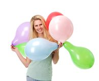 Lyckliga innehavballonger för ung kvinna Arkivbild