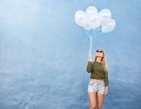 Lyckliga innehavballonger för ung kvinna Arkivfoto