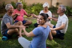 Lyckliga instruktörinnehavhänder med högt folk, medan meditera Royaltyfria Bilder