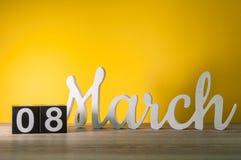Lyckliga internationella dagar för kvinna` s Mars 8th Dag 8 av månaden, daglig träkalender på tabellen med gul bakgrund Royaltyfri Bild