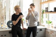 Lyckliga internationella glade par hemma i tillf?lliga kl?der Dricka kaffe i k?ket fotografering för bildbyråer