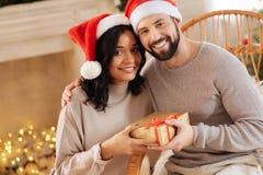 Lyckliga internationella par som poserar med julklapp Royaltyfri Foto
