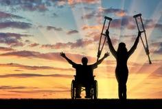 Lyckliga invalids med kryckor och i rullstolsolnedgång royaltyfri bild